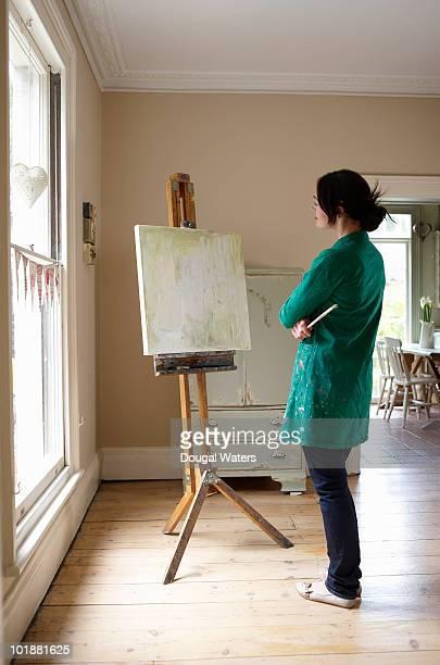 Woman contemplating art work.