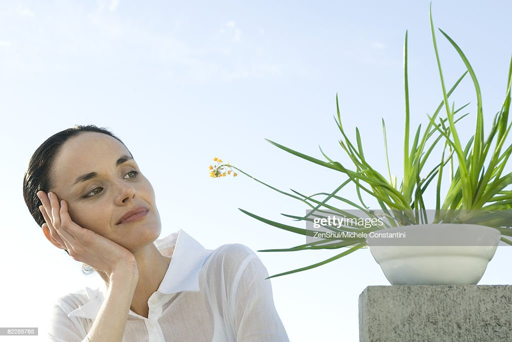 Woman contemplating plant : Stock Photo