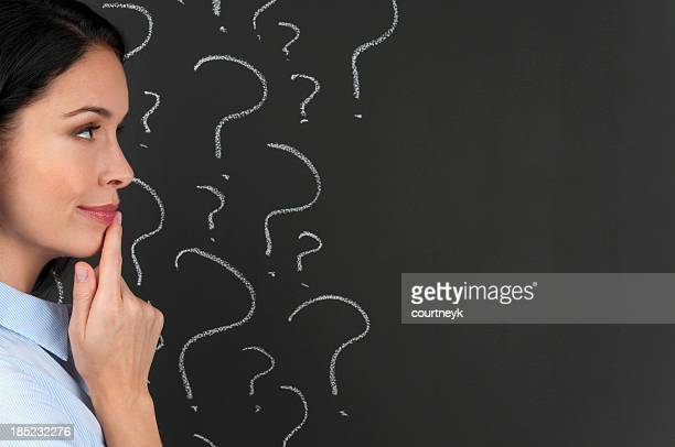 Woman contemplating question marks