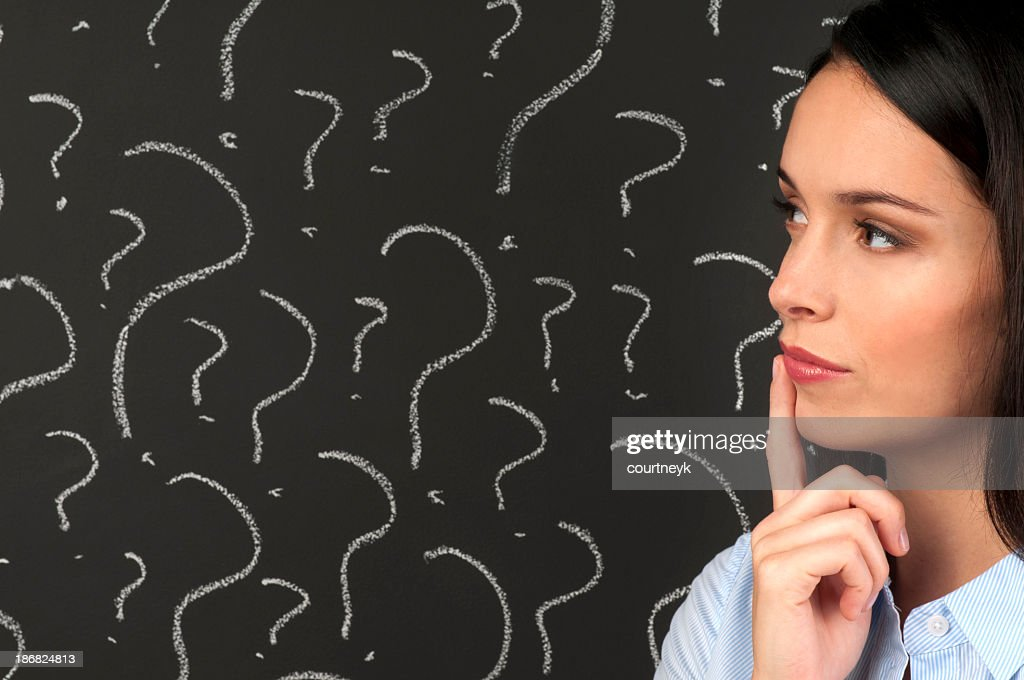 Woman contemplating question marks : Stock Photo