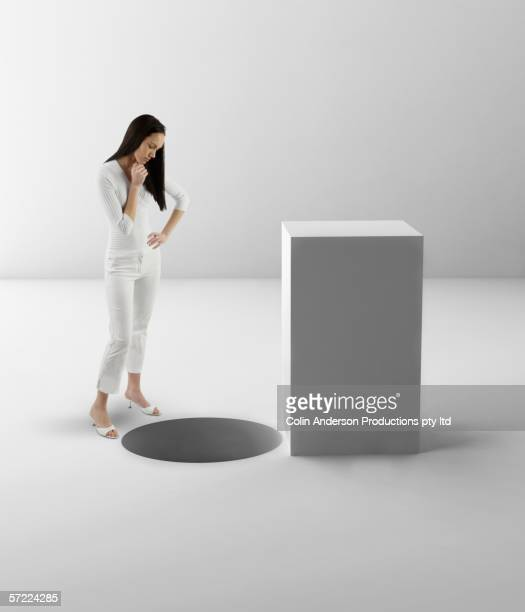 Woman contemplating square peg and round hole