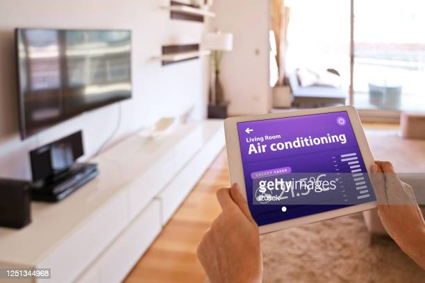 woman controlling air conditioner with a digital tablet at home - ventilator stock pictures, royalty-free photos & images