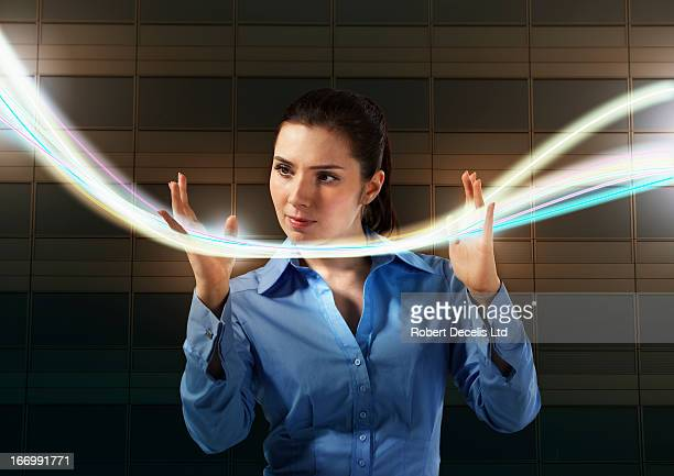 woman controlling lightrails through fingers - light trail stock pictures, royalty-free photos & images
