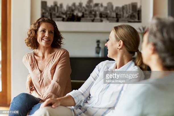 woman conversing with friends at home - alleen vrouwen stockfoto's en -beelden