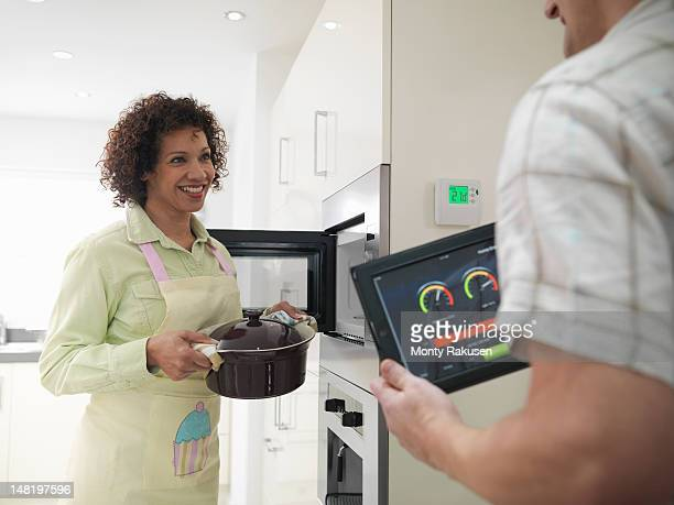 Woman cooking as husband checks energy tracking application on digital tablet