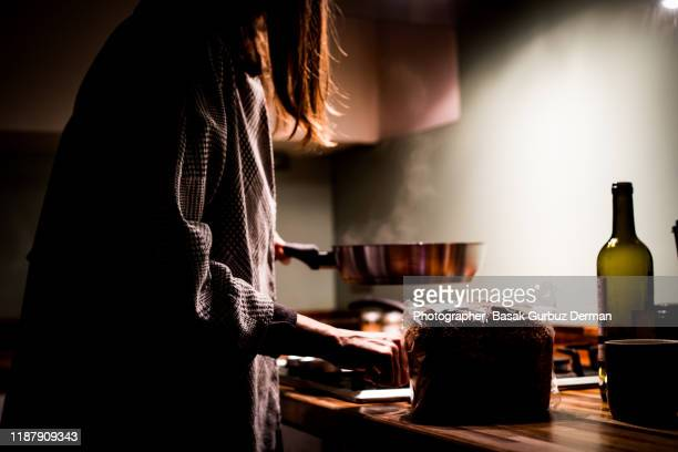 a woman cooking at night in the kitchen - domestic kitchen stock pictures, royalty-free photos & images