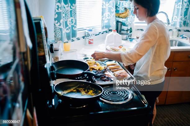Woman cooking breakfast in kitchen