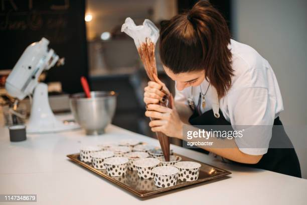 mujer cocinando cupcakes - cupcake fotografías e imágenes de stock