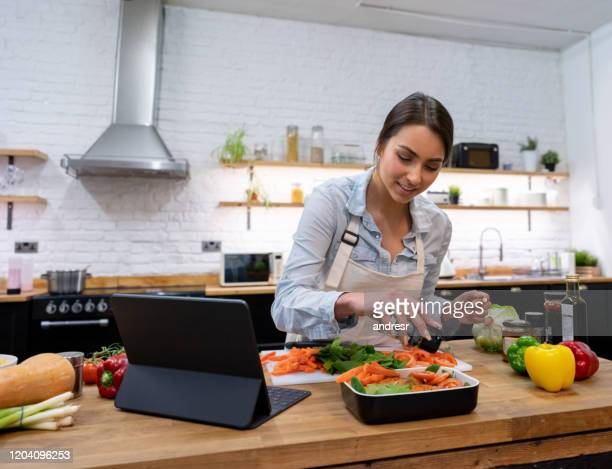 woman cooking dinner following an online recipe - following stock pictures, royalty-free photos & images