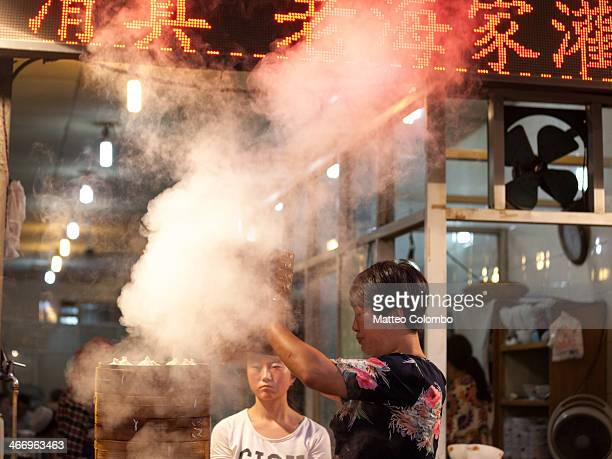 Woman cooking dumplings with steam, at the night street food market in the muslim quarter of Xian, Shaanxi, China