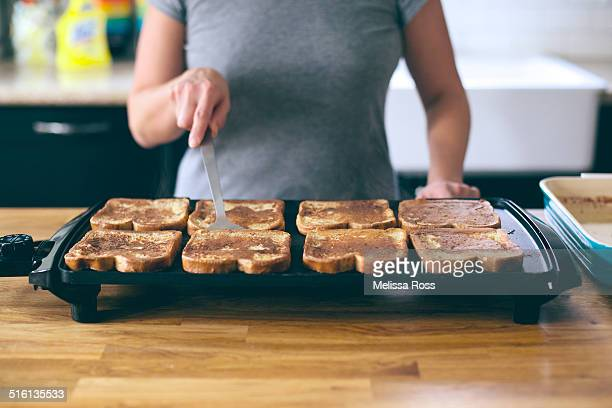 Woman cooking french toast on a griddle.