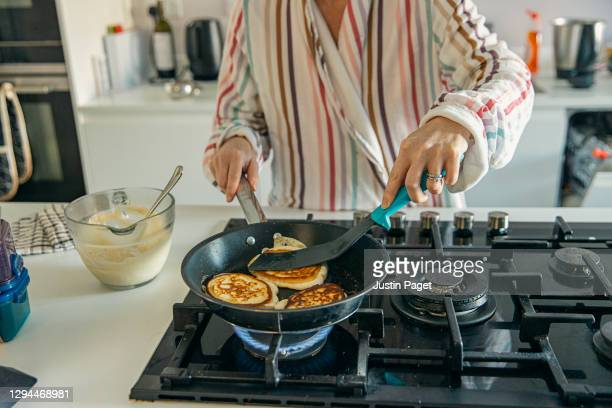 woman cooking homemade pancakes for breakfast - making stock pictures, royalty-free photos & images