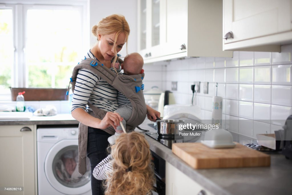 Woman cooking in kitchen, baby strapped to body in sling, daughter standing beside her : Stock Photo