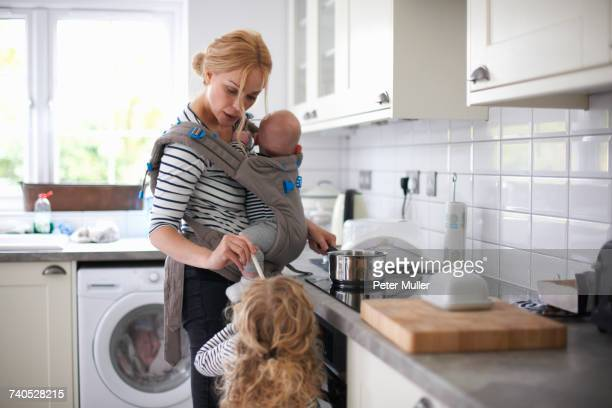 Woman cooking in kitchen, baby strapped to body in sling, daughter standing beside her
