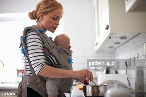 Woman cooking in kitchen, baby strapped to body in sling