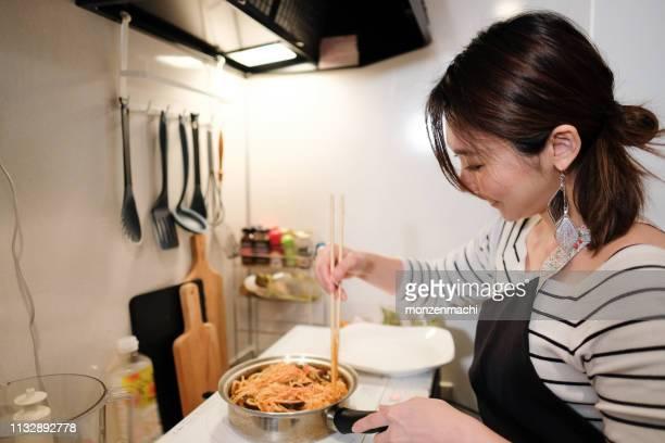 キッチンでの女性の調理 - 専業主婦 ストックフォトと画像
