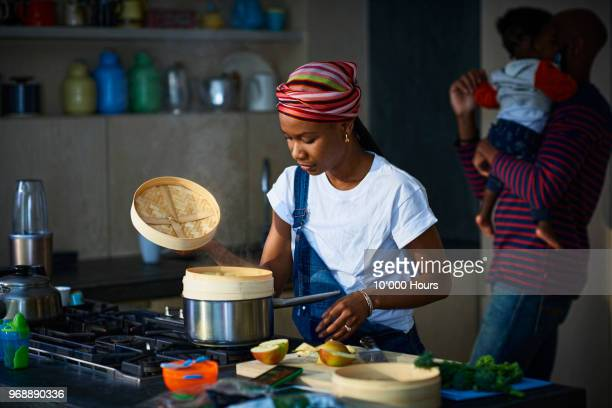 woman cooking in kitchen - black cook fotografías e imágenes de stock
