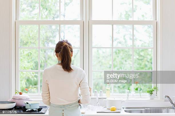 Woman cooking in kitchen, rear view