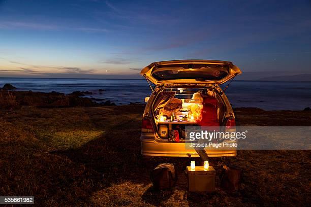 Woman cooking in minivan at twilight