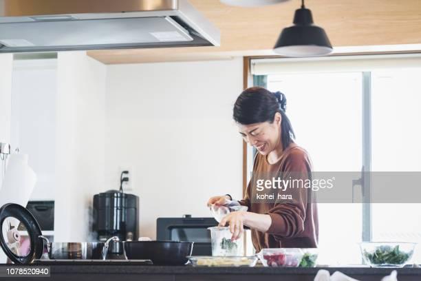 台所で料理をする女性 - キッチン ストックフォトと画像