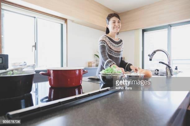女性のキッチンで調理 - 30代の女性 ストックフォトと画像