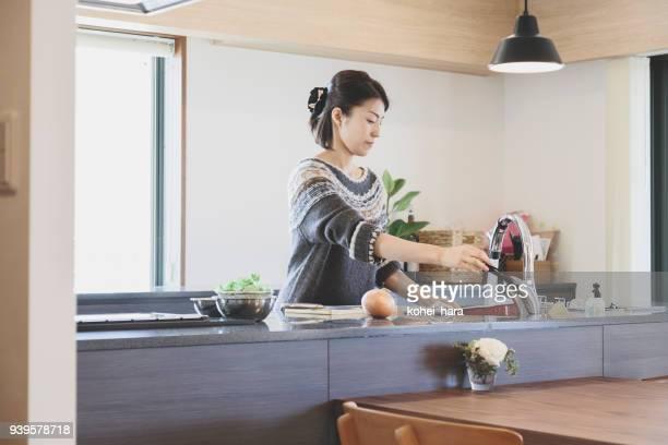 女性のキッチンで調理 - 人がつくり出したもの ストックフォトと画像