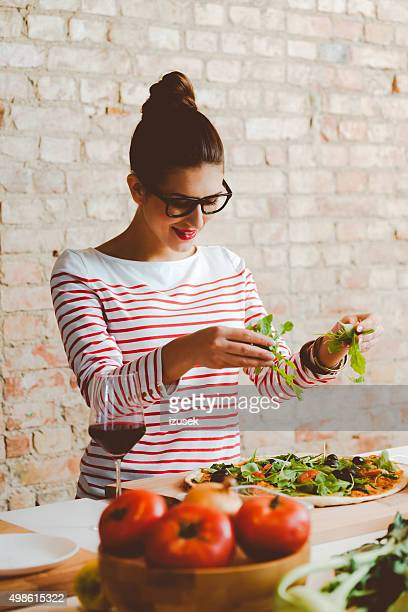 Woman cooking in the modern kitchen, preparing pizza