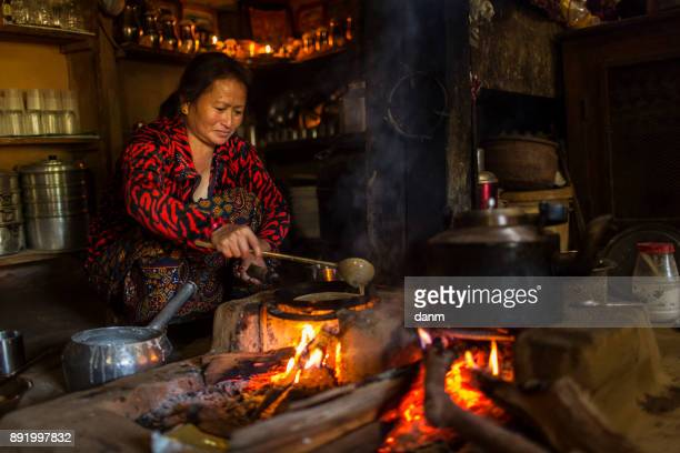 Woman cooking inside of traditional house of Himalayan Village on November 19, 2017 in HIMALAYAN VILLAGE, Nepal
