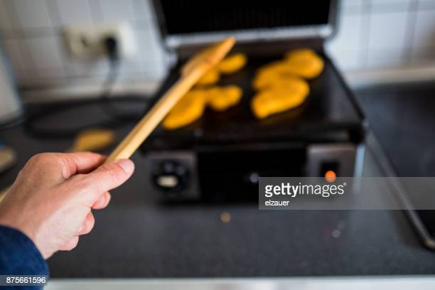A woman cooking nuggets.