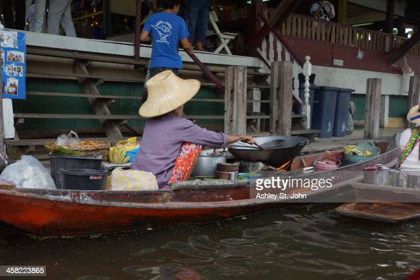 Woman cooking on a boat at the floating market in Damnoen Saduak, Rachaburi Provence, Thailand, in October 2013.