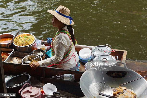 Woman cooking on a boat in the Damnoen Saduak floating market in Rachiburi, Thailand, in October 2013.