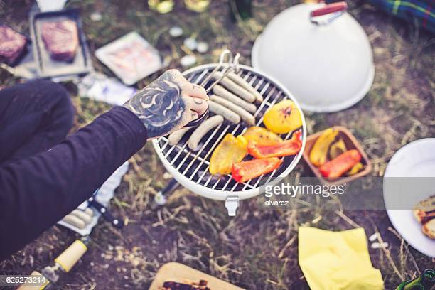 Woman cooking sausage on portable barbecue