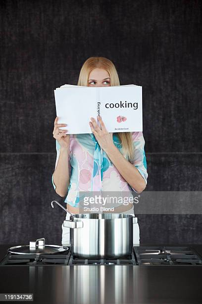 Woman cooking, thinking about the recipe.