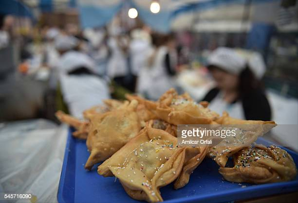 A woman cooking typical fried food Pastelitos stuffed with quince or sweetpotato during Argentina Bicentennial Celebrations at Feria de Mataderos on...