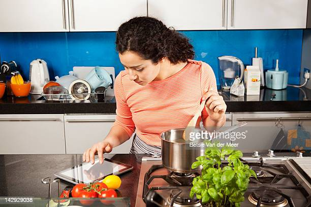 Woman cooking while looking on i pad at recipe.