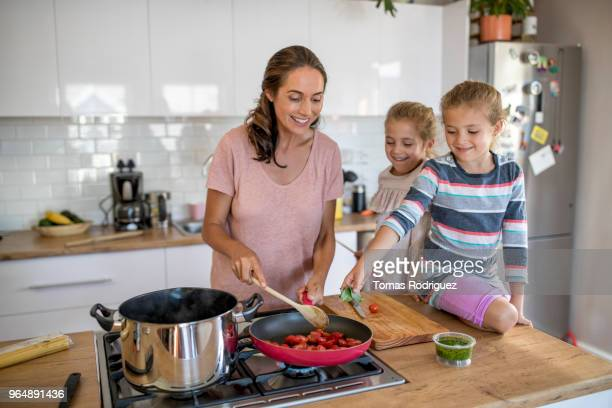 Woman cooking with twin girls in a kitchen