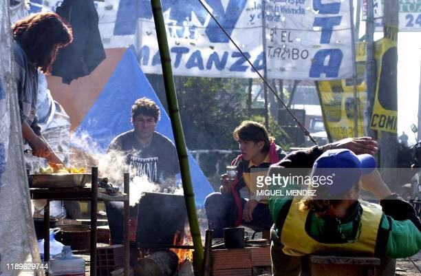 Woman cooks as her family rests outside their tent in Matanza, a province of Buenos Aires, Argentina, 19 May 2001. Una mujer cocina, mientras el...