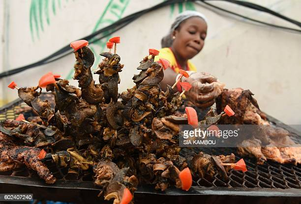 A woman cooks braised snails on September 11 2016 in Abidjan during the 9th edition of the 'Festival des Grillades d'Abidjan' / AFP / Sia KAMBOU