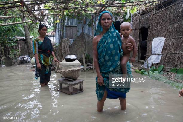 A woman cooks food and other women stands with her gradchild in front of her flooded house near a river Padma at Dohar Nawabganj Bangladesh 19 August...