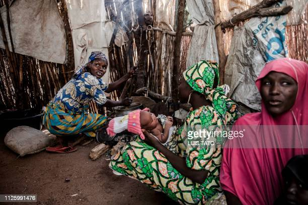 A woman cooks inside her home at Malkohi refugee camp in Jimeta Adamawa State Nigeria on February 19 four days ahead of the country's General...