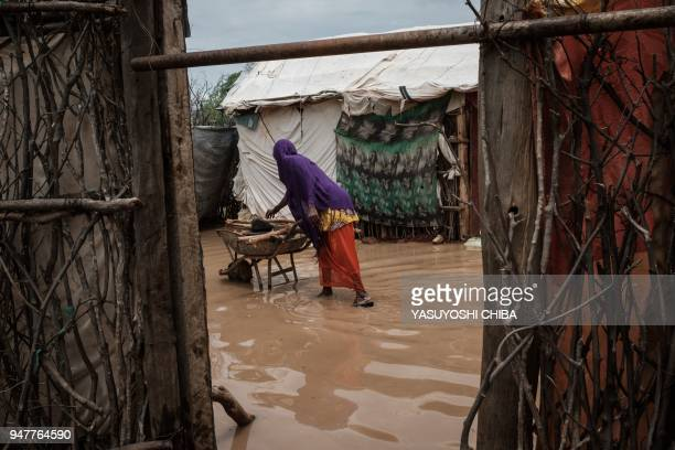 Woman cooks on a wheelbarrow beside flooded shelters after a heavy rainy season downpour at the Dadaab refugee complex, in the north-east of Kenya,...