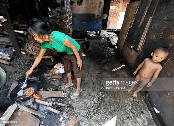 A woman cooks with an open fire pit at a slum area in downtown Jakarta on October 11 2010 Having successfully negotiated the global financial crisis...
