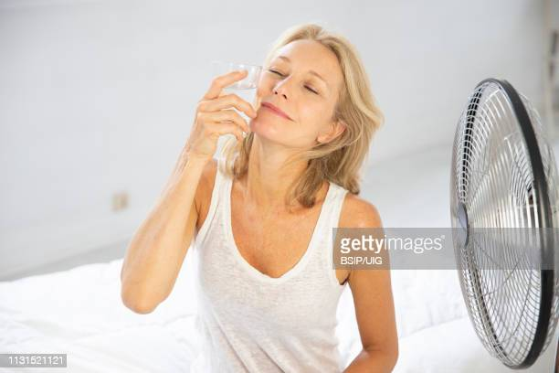 woman cooling down with a fan and glass of water. - menopause stock pictures, royalty-free photos & images