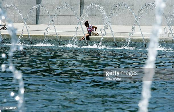 Woman cools herself off by the fountain as she visits the World War II Memorial July 17, 2006 in Washington, DC. The weather forecast predicted the...