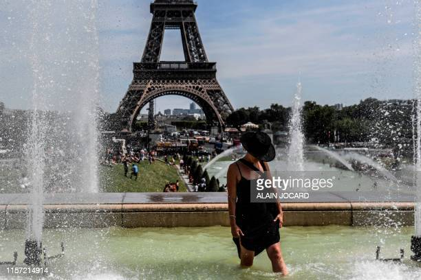 TOPSHOT A woman cools off at the Trocadero Fountains near the Eiffel Tower in Paris on July 22 2019 Parisians were on July 22 2019 bracing for...