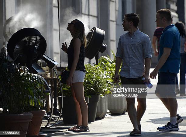 A woman cools off with a fan displayed on a terrace of a bar during a heatwave in Madrid on June 28 2015 A powerful heatwave was forecast to sweep...