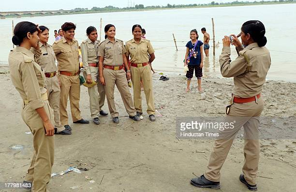 A woman cop clicks picture of her colleagues at the Saryu Ghat as normalcy returned on August 26 2013 in Ayodhya India High security was on alert in...