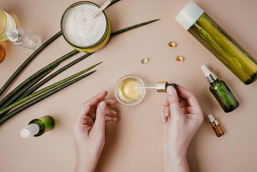 Woman cosmetologist cosmetics testing. Natural organic cosmetics. Serum hair mask. Flat lay pastel 1164263699