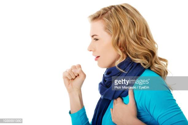 woman coughing against white background - cough foto e immagini stock