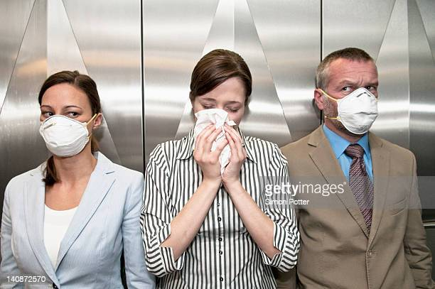 woman coughing around others in elevator - sneezing stock pictures, royalty-free photos & images